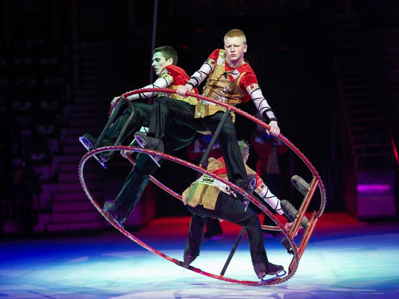 Трое парней крутятся в одном гимнастическом колесе в коньках на льду шоу московского цирка на льду