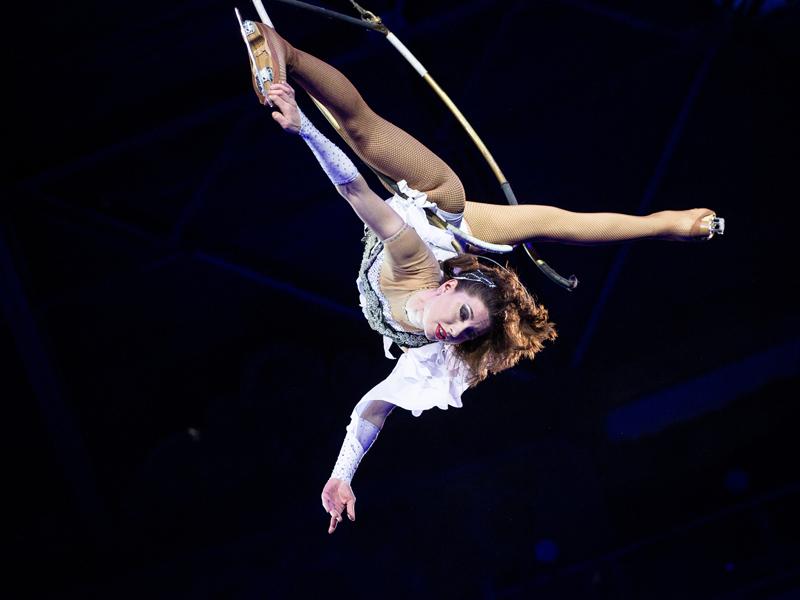 Девушка в коньках в шпагате в низ головой на воздушном кольце цирк на льду