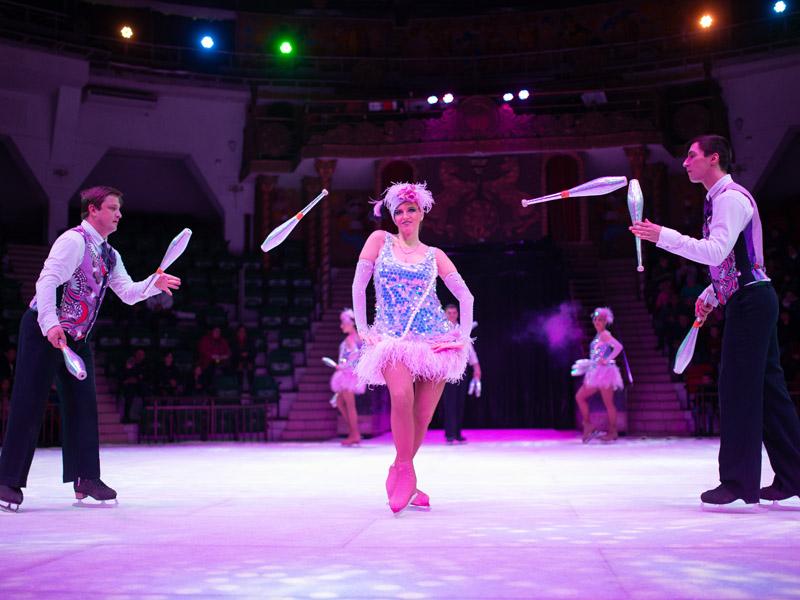 Жонглеры на льду кидают булавы вокруг девушки на коньках