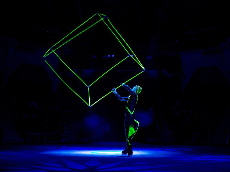 Мужчина крутит люминисцентный куб в темноте на коньках