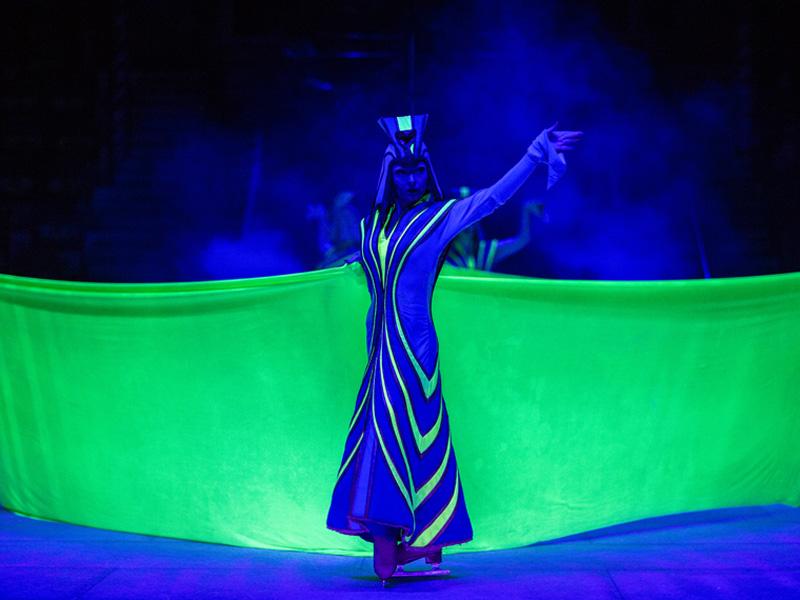 Девушка вдлинном египетском платье скрывает чт-то за люминисцентной тканью