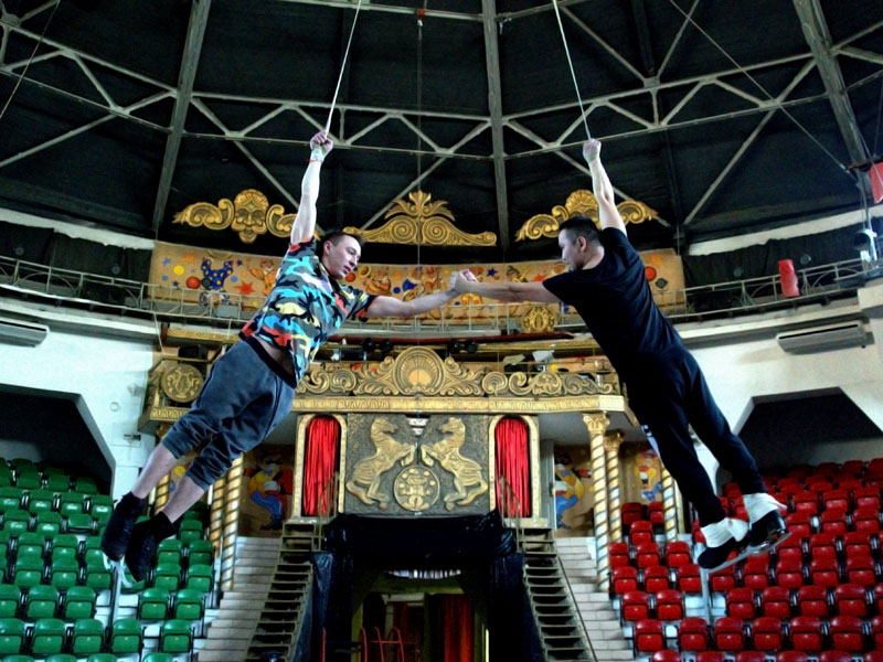 Два парня на воздушных ремнях дежат друг друга на вытянутой руке