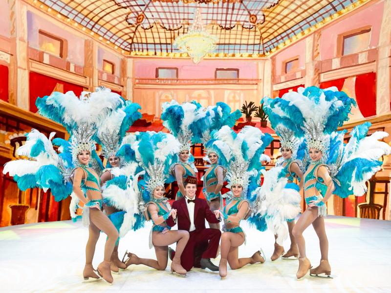 Цирк на льду Гранд Отель портье окружен девушками в перьях на льду