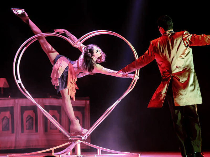Girl on skates in a heart shaped spinning ring with maitre d'hotel at Grand Hotel by Moscow circus on ice
