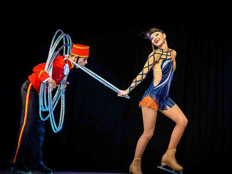 Girl on skates drags lobby boy with hoola-hoop at Grand Hotel by Moscow circus on ice