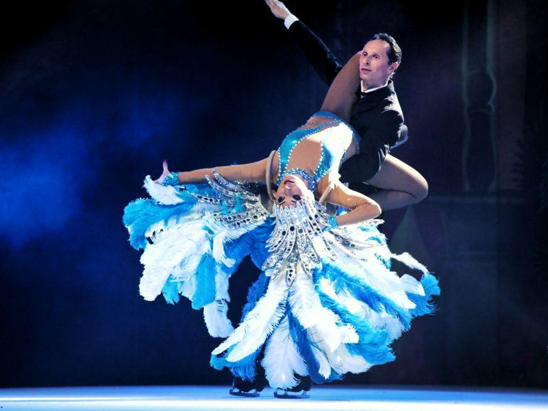 Wedding dance of girl in furs an black suit man on ice at Grand Hotel by Moscow circus on ice