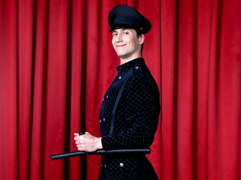 Smiling policeman profile in front of red curtain at Grand Hotel by Moscow circus on ice