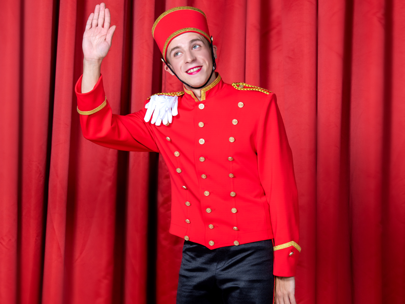LObby boy waving hand in front of red curtain at Grand Hotel by Moscow circus on ice