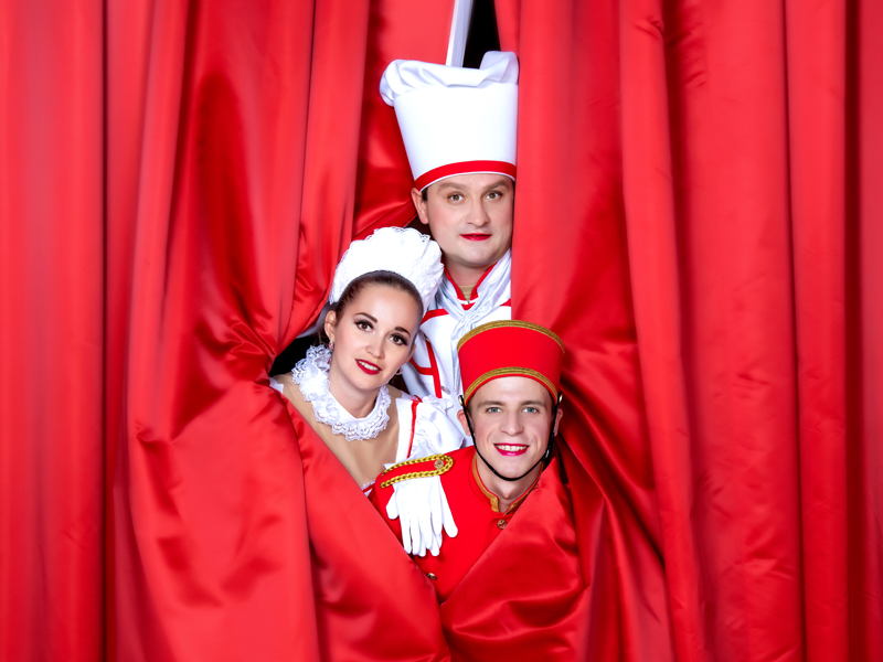 Cheef cook, maid and Lobby-boy smiling from the red curtain at Grand Hotel by Moscow circus on ice